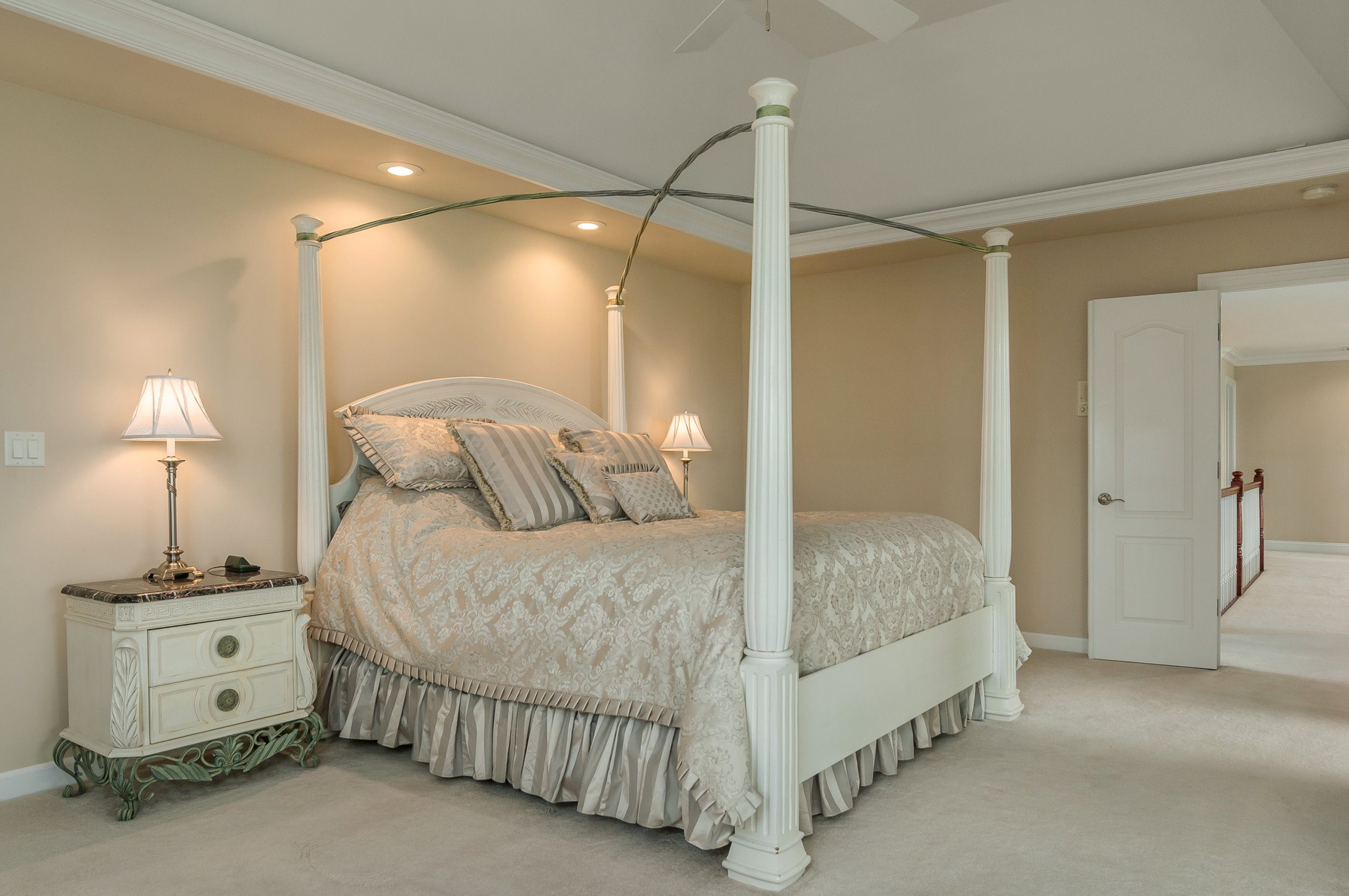 Off white themed luxury master bedroom in estate home in Somonauk, Ilinois.