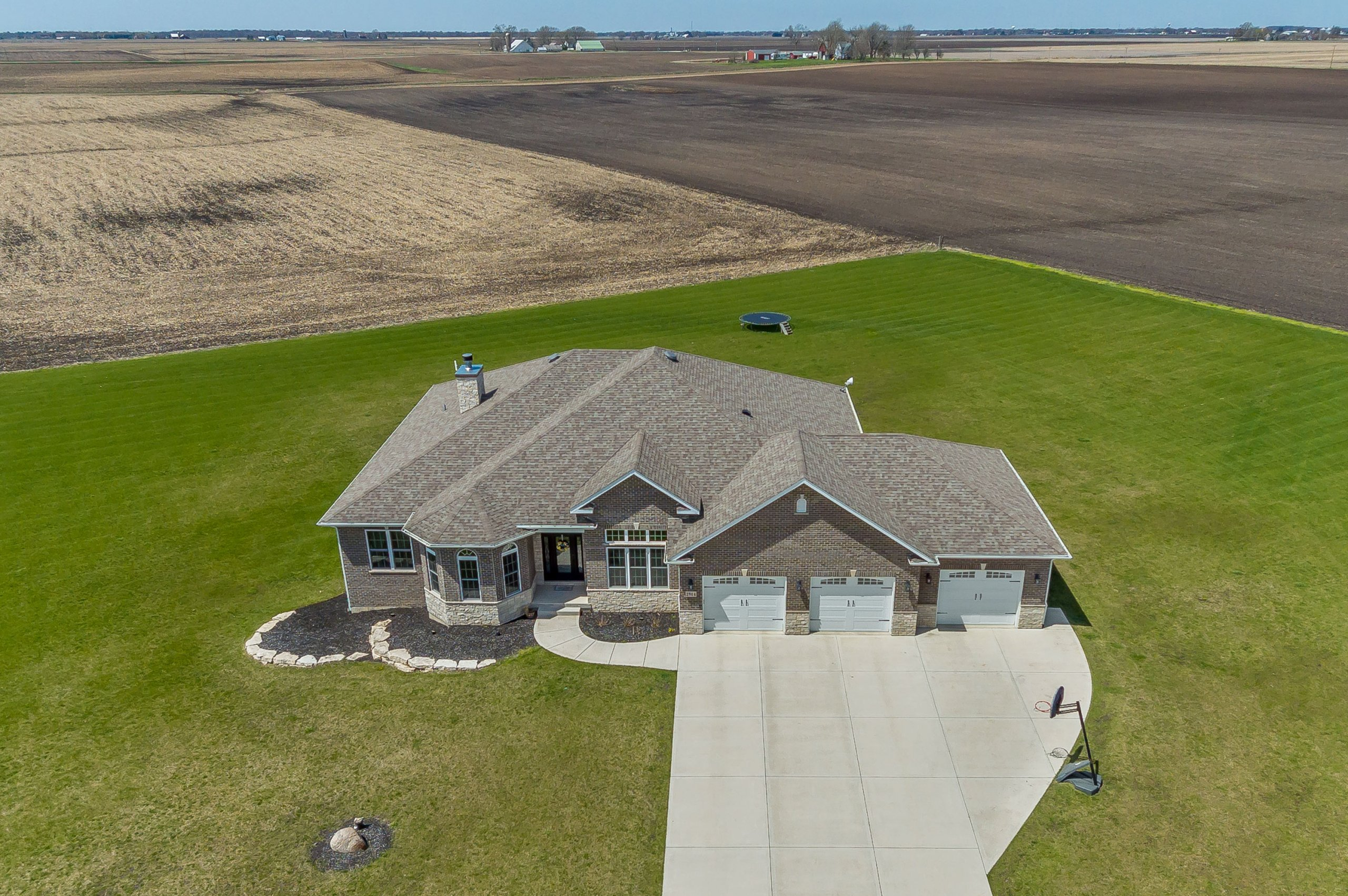 Drone aerial of new, custom brick home in Sheridan, Illinois.