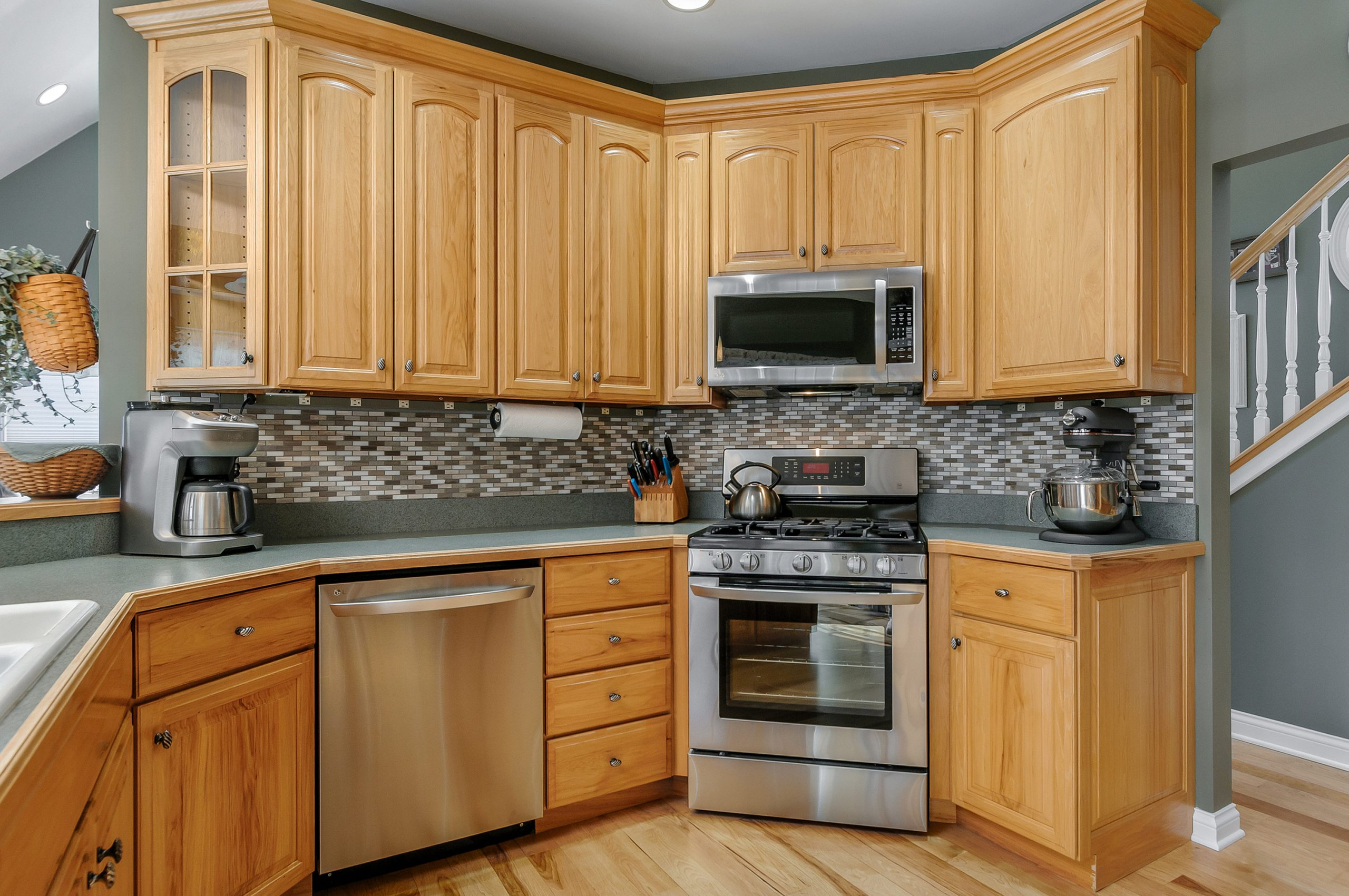 Natural maple kitchen with stainless steel appliances.
